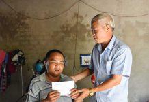 Ông Nguyễn Văn Hùng-Chủ tịch Hội Người mù tỉnh tặng quà cho anh Dàu. Ảnh: H.P