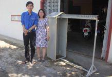 Em Trần Kế Tuấn Vương và cô giáo Tạ Thị Hạnh bên chiếc máy phơi đồ.  Ảnh: H.S