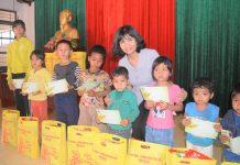 Bà Rcom Sa Duyên tặng quà cho trẻ em nghèo xã Ia Pnôn. Ảnh: Đinh Yến