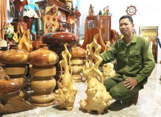 Anh Quách Văn Lâm (xã Bờ Ngoong, huyện Chư Sê) giới thiệu về những chiếc lộc bình làm bằng gốc cà phê. Ảnh: Nhật Hào
