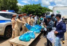 Lực lượng Cảnh sát Giao thông tỉnh hỗ trợ lương thực cho người dân về từ các tỉnh phía Nam tại chốt kiểm soát phòng-chống dịch Covid-19 khu vực cầu 110 (huyện Chư Pưh). Ảnh: Lê Anh